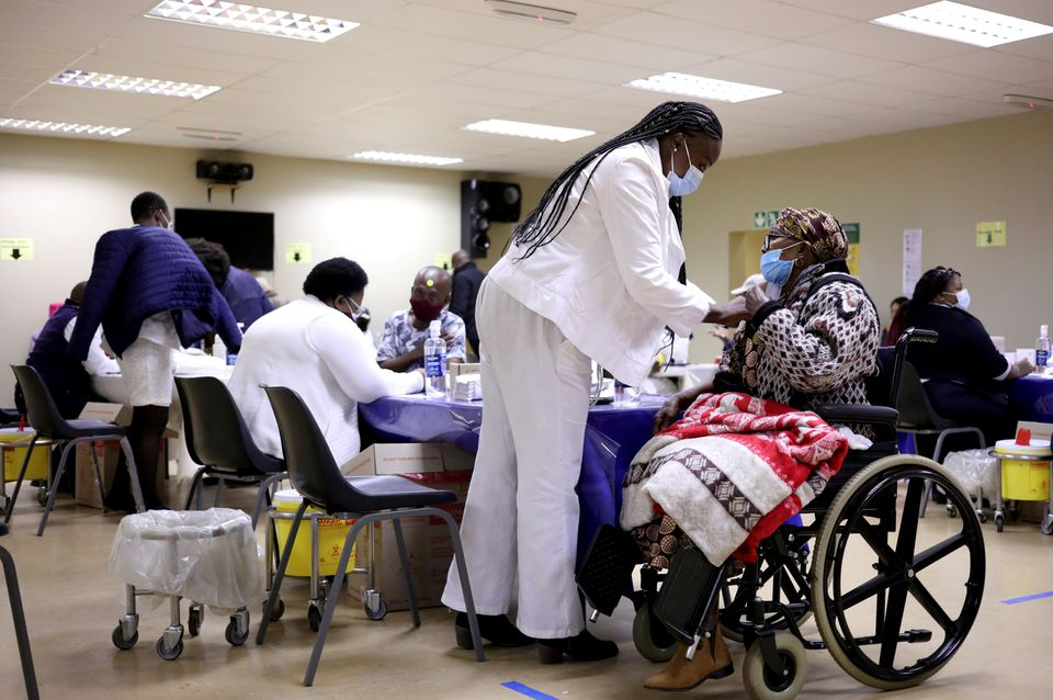 A woman receives a dose of a coronavirus disease (COVID-19) vaccine, as South Africa rolls out the coronavirus disease (COVID-19) vaccination to the elderly at the Munsieville Care for the Aged Centre outside Johannesburg, South Africa May 17, 2021. REUTERS/Siphiwe Sibeko/File Photo